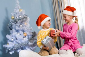 6091844 - portrait of happy siblings exchanging christmas gifts at home