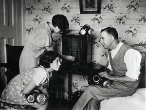World War Two. England. 1938. The family at home, tuning in to hear the news on the radio news. They have gas masks at the ready.